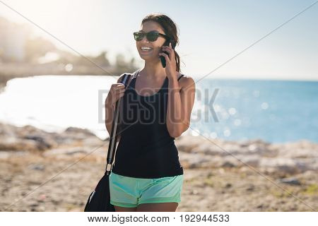 Young Pretty Woman On Beach Talking On Mobile Laughing