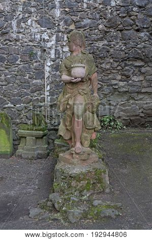The photo shows an old stone sculpture depicting a woman figure. The woman has a dress that is folded above her knees, her long, stiff hair. The head is facing right. In clay hands clay pot garlic. The sculpture stands on a stone, low plaza. It is covered