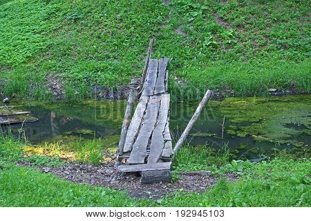 The photograph depicts a carelessly made, devastated wooden footbridge. It is made of rough boards. It is flush over the standing, covered lashes with water. The shore is covered with green grass. It's daytime.