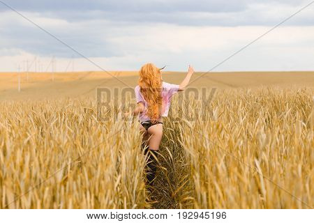 Portrait of happy long haired woman running away on wheat field