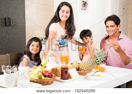 An attractive happy, smiling Asian Indian family of mother, father, son and daughter eating healthy food & salad at a dining table. Indians eating breakfast, lunch or dinner. Selective focus