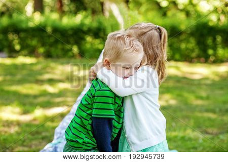 Children hug in the garden. 2-3 years. Girl and boy. The concept is childhood and family.