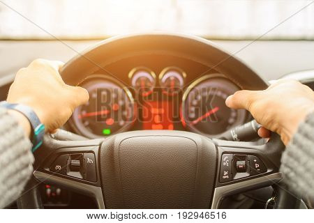 Man ready for driving the car on the freeway. Close up of hands of driver on steering wheel of car. Personal point of view of machine's