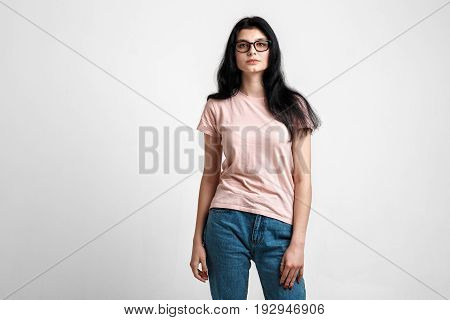 Portrait of smart beautiful brunette girl in eyeglasses with natural make-up, on grey background