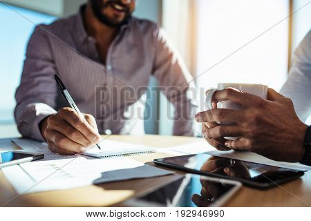 Businessman writing in notepad while his partner holds a coffee cup. Two businessmen in a discussion at office.