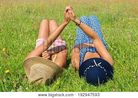 Two young women lying together in green grass