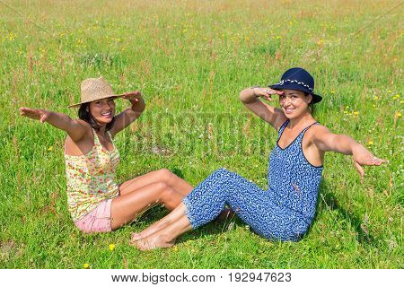Two friends wearing summer hats saluting in green meadow