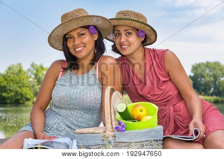 Two friends with hats and picknick basket at water in nature