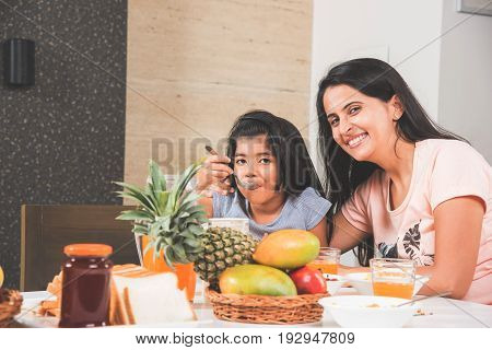 An attractive happy, smiling Asian Indian family of mother and daughter eating healthy food & salad at a dining table. Indians eating breakfast, lunch or dinner. Selective focus