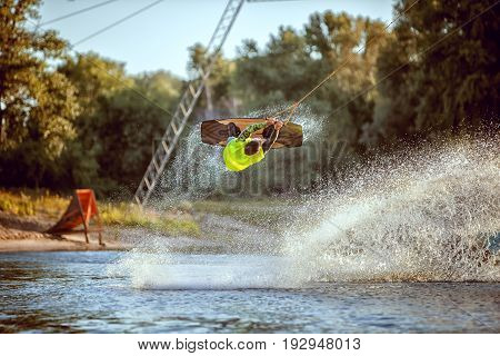Above the water sportsman wakeboarder performs jumping trick.