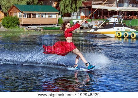 Woman enjoys skating on the lake on a wakeboard.