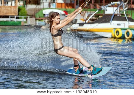 Young woman on a board slides on water.