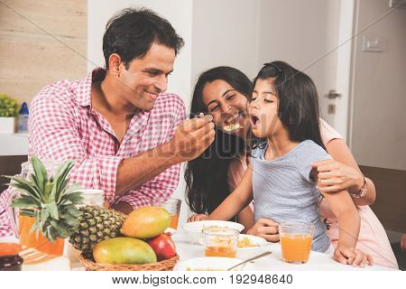 An attractive happy, smiling Asian Indian family of mother, father and daughter. Father feeding cereal to daughter with spoon at dining table. Indians eating breakfast, lunch / dinner. Selective focus