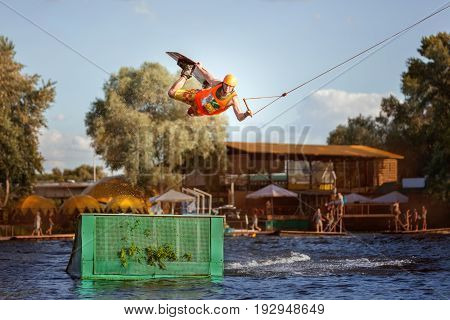 Male skateboarder jumps over a springboard on a lake he is an extreme sportsman.