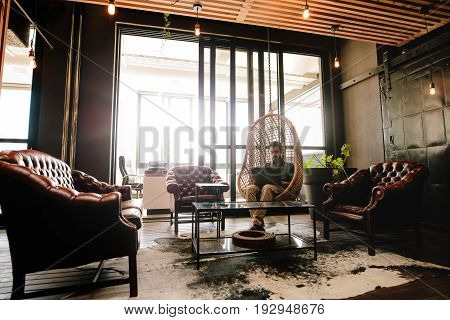 Young businessman sitting in a modern corporate environment. Man relaxing in office lounge and working on laptop computer.