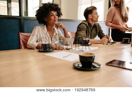 Shot of young african business woman sitting around table with colleagues during staff meeting in office conference room.