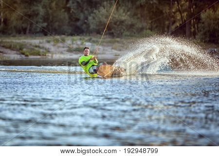 Wakeboarder surfing across the lake by water skiing.