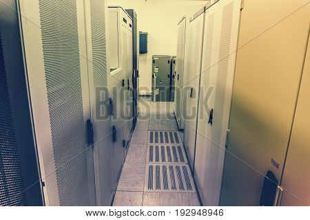 Data center server room, Switchgear room with raws of cabinets with network or cellular hardware, perspective, toned