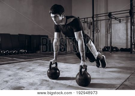 Gym man push-up strength pushup exercise with Kettlebell in a fitness workout