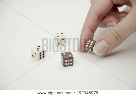Hand placing dice on white background close up.