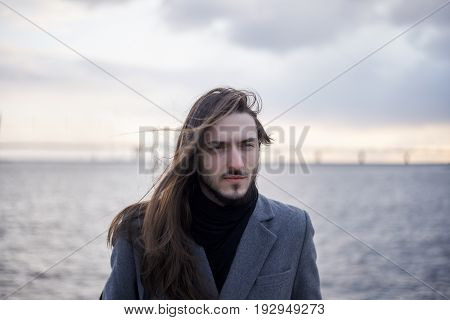 Lonesome melancholic young male with beard wearing his long brunette hair loose posing against river and cloudy sky background dressed in stylish coat feeling depressed after quarrel with girlfriend