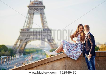 Beautiful Loving Couple Sitting Near The Eiffel Tower In Paris