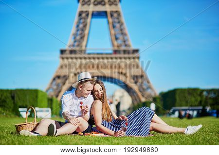 Couple Having Picnic Near The Eiffel Tower In Paris, France