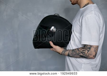 Cropped profile portrait of bearded Caucasian motorcyclist with tattooed arm holding black shiny protective helmet in front of him ready for extreme ride on streets of night city with friends