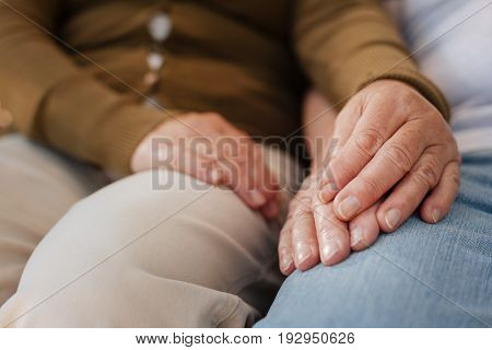 I believe you. Senior people spending time together and sitting next to each other while touching hands
