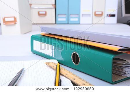 Folder file, note and pen on the desk. blurred background