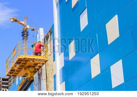 A worker installs panels facing on the facade of the house