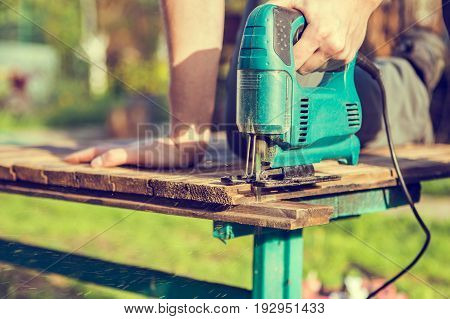 Worker saws board in park with electric jigsaw