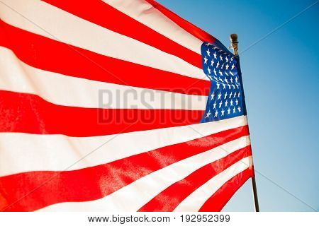 American flag with blue sky and sunlight for Memorial Day or 4th of July.