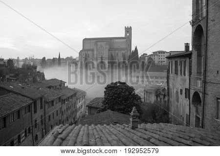 Italy Siena - December 26 2016: the view of red tiled roofs and Basilica Cateriniana of San Domenico in the mist on December 26 2016 in Siena Tuscany Italy.