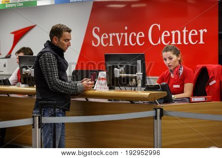 VIENNA/ AUSTRIA - APRIL 6, 2017. Service center at the Vienna airport Schwechat, Austria. An employee helps a passenger to obtain the necessary information.