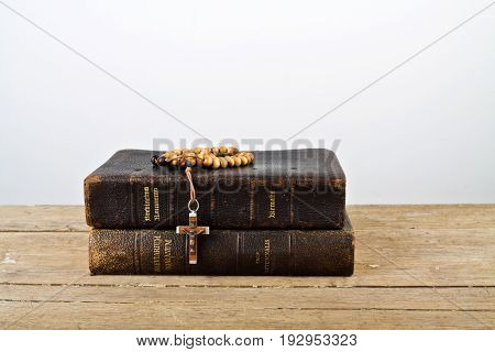 The books of Catholic Church liturgy and rosary beads on the wooden table