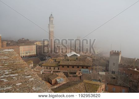 Italy Siena - December 26 2016: the view of Torre del Mangia in Piazza del Campo and red roofs of Siena in mist on December 26 2016 in Siena Tuscany Italy.