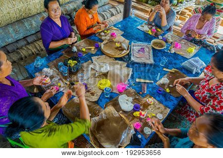 BALI, INDONESIA - MARCH 08, 2017: Women preparing an Indian Sadhu dough for chapati on Manmandir ghat on the banks of the holy river Ganges in Varanasi.