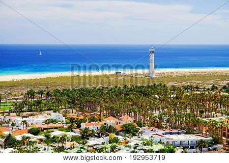 Aerial view on Morro Jable with homes for holidays with green palm trees around a lighthouse the beach with golden sand Playa de Morro Jable or Marorral and white sailboat in the Atlantic Ocean. Canary Island Fuerteventura Spain.