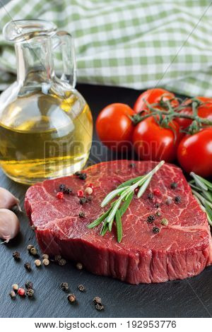 Raw steak with knife, spices and ingredients for cooking.