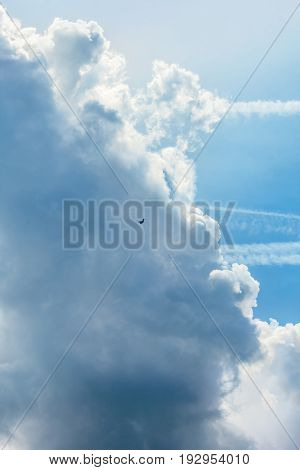 Blue sky with white clouds and contrails on a summer day close-up