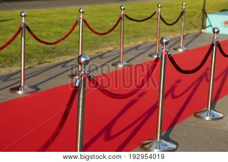 Long red carpet between rope barriers on VIP entrance.
