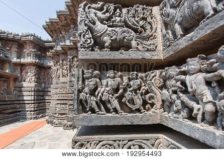 Ancient people and myth lions on old wall of temple. Sculpured stone relief carvings from the 12th century temple in Karnataka. Old Indian artwork.