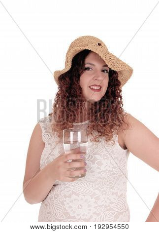A young pretty woman in a white dress and straw hat standing waist up and holding a glass of water isolated for white background.