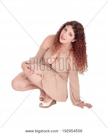 A beautiful woman with big breasts crouching on the floor in a short beige dress and curly hair isolated for white background.
