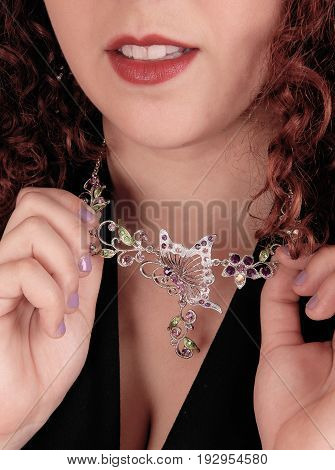 A closeup image of a beautiful necklace around the neck of a young woman holding her necklace.