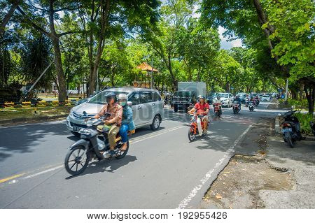 .BALI, INDONESIA - MARCH 08, 2017: Unidentified people driving motorcycles and cars in the road full of traffic. The government says Bali streets could be gridlocked in five years with vehicle sales growing by 12.3 percent a year, in Denpasar Indonesia.