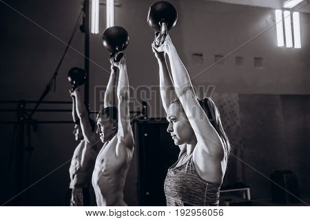 Healthy fit young athletes doing exercises with kettlebells at gym, men and women during weight lifting workout.