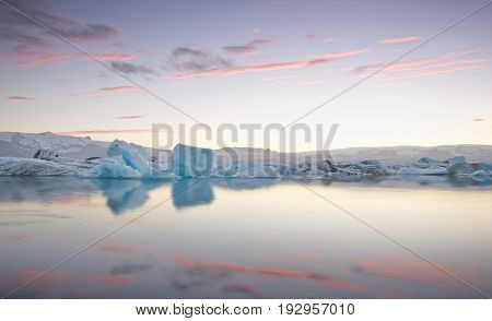 Giant pieces of ice flowing on and reflecting in cold lake with a huge glaciar behind, jokulsarlon glaciar lagoon, Iceland