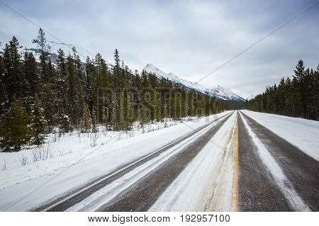 Long empty winter road leading to mountains, Banff national park, Canada